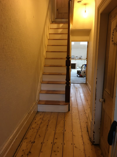 Finished shot of hallway pine flooring and original timber staircase with treads and risers restored